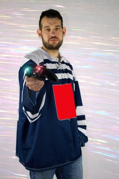 Man in hockey sports dress gives you a controller from the game console. Let`s play and qualify for the electronic sport Olympics.