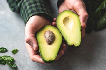 Avocado in male hands. Halved ripe avocado. Healthy vegan vegetarian food concept