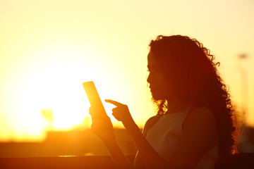Silhouette of a woman checking phone at sunset
