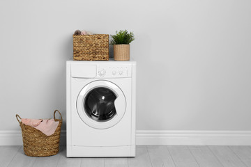 Modern washing machine with houseplant and laundry baskets near white wall. Space for text