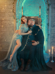 Pretty woman queen seduces king. Men in golden crown sits old iron throne with glass wine. Luxury velvet royal clothes. Sexy concubine harem. Creative design silk blue dress bare legs. backdrop room