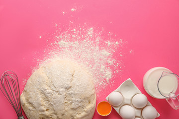 Raw dough and ingredients for pastries on pink background, flat lay. Space for text