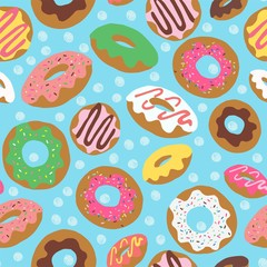Seamless repeat pattern with colourful colorful donuts doughnuts with sprinkles and icing tossed on a blue background with scribbled drawn sketched dots