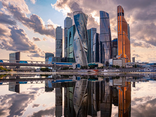 Photo sur Toile Lavende Urban landscape of steel color. Skyscrapers of Moscow are reflected in the water. Moskva-city. Tall buildings and gray clouds. Reflection. Panorama of modern Moscow.