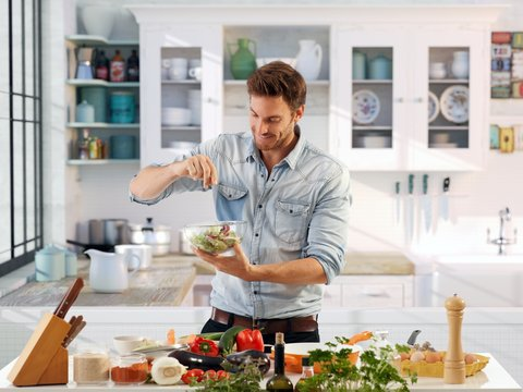 Casual man preparing salad