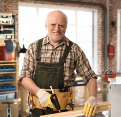 Senior happy handyman working at DIY workshop