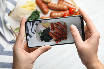 Blogger taking photo of grilled sausages with garnish at white table, closeup