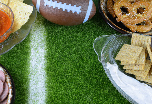 Snacks for watching a football game. Great for Super Bowl or Playoff themed projects. Pretzels, sausage, chips and dips with a football and a faux grass background