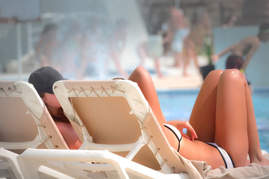 Low Section Of Seductive Woman Resting On Lounge Chair At Beach