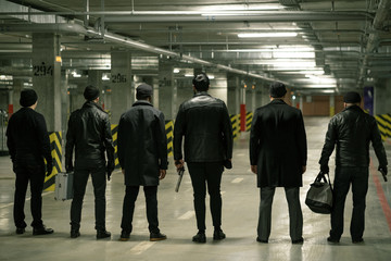 Rear view of row of criminals or gangsters in black standing on parking area