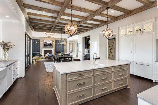 Beautiful open concept kitchen, dining room, and living room in new luxury home, with hardwood floors, fireplace, and dining table.