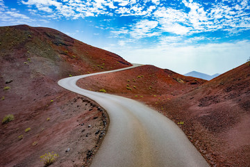 Self adhesive Wall Murals Deep brown Image related to unexplored road journeys and adventures.Road through the scenic landscape to the destination in Timanfaya natural park in Lanzarote,Canary island,Spain