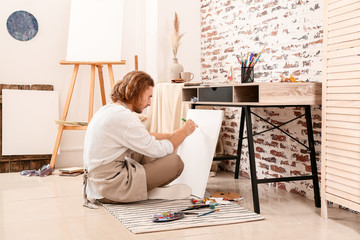 Young male artist painting at home Wall mural