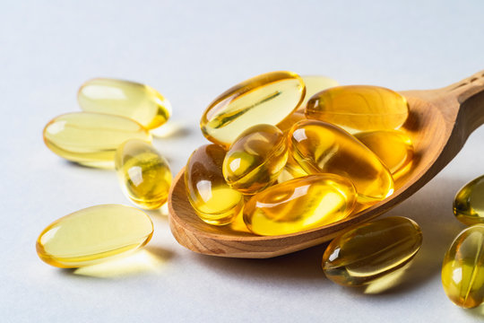 Omega 3 yellow capsules in wooden spoon on white background. EPA and DHA are two types of Omega-3 fats Essential Fatty Acids.