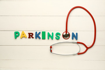 Text PARKINSON with stethoscope on white wooden background
