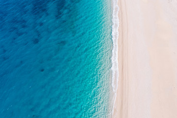 Top-down aerial view of a white sandy beach on the shores of a beautiful turquoise sea.