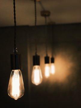 Close-Up Of Illuminated Light Bulb Hanging At Home