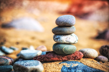 Poster Stones in Sand Sea pebble stones tower on beach. Balance and harmony concept