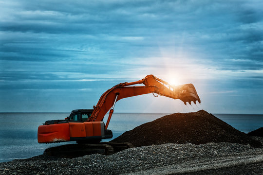 backhoe or digger working with bucket at industrial earth excavation site in sunrise light