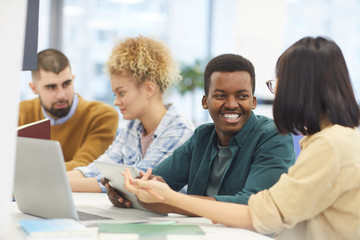 Multi-ethnic group of students studying in college library, focus on African-American man smiling at partner
