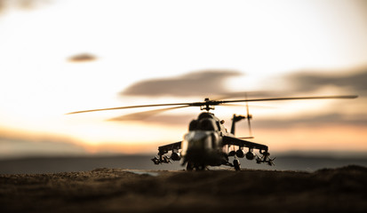 Stores photo Hélicoptère Silhouette of military helicopter ready to fly from conflict zone. Decorated night footage with helicopter starting in desert with foggy toned backlit. Selective focus.