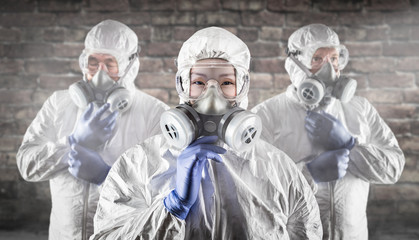 Chinese Woman and Team Behind In Hazmat Suites, Gas Masks and Goggles Against Brick Wall