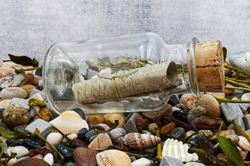 Message in a bottle on a beach with stones and shells. Studio shot