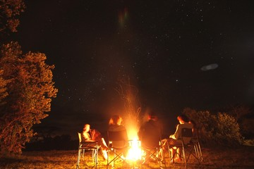 people sitting around campfire AT NIGHT Wall mural