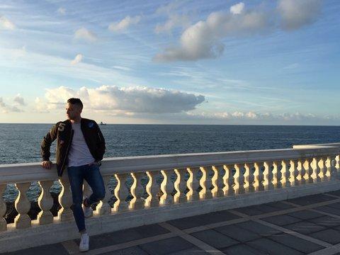 Full Length Of Man Leaning On Railing Against Sea