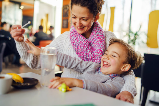 Young woman mother with small boy child son having fun at cafe or restaurant caucasian kid smiling while sitting by the table teasing playing