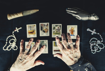 Old woman holding her hands above tarot cards. Old wrinkeld hands. Occult fortune telling concept. Picture taken from above.