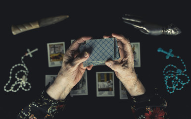 Old woman shuffle tarot cards above other tarot cards. Old wrinkeld hands. Occult fortune telling concept. Picture taken from above.