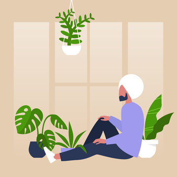 Young indian male character sitting by the window surrounded by house plants, meditative relaxation