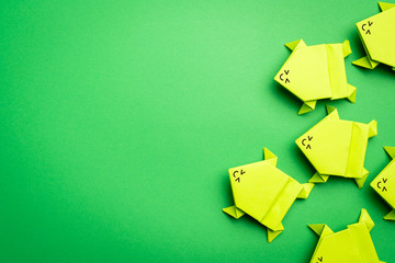 Fotobehang Kikker Group of origami green paper frogs isolated on green background