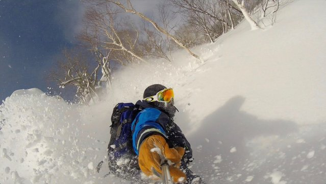 High Angle View Of Man Holding Monopod While Splitboarding On Snowy Mountain