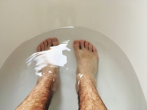 Low Section Of Man Relaxing In Bathtub