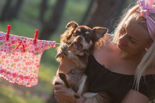 Close-Up Of Smiling Woman Carrying Chihuahua