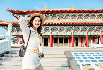 Fotobehang Bedehuis happy Young backpacker woman stand before traditional chinese temple