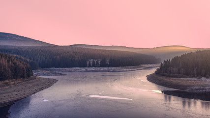 Frozen dam in the winter forest at sunset. A pink illuminated sky above Ecker Reservoir and Ecker Dam near Bad Harzburg, Harz mountain range, Lower Saxony/Saxony-Anhalt, Germany.