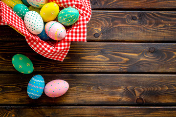 Basket with painted eggs for Easter dinner on dark wooden desk top-down copy space