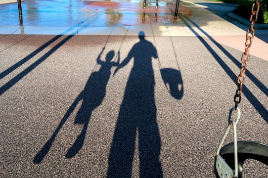 Shadow Of Father And Kid On Footpath At Playground