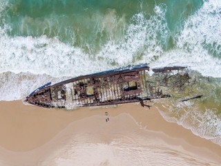 High angle aerial bird's eye drone view of the SS Maheno shipwreck, an ocean liner which ran aground on Seventy-Five Mile Beach on Fraser Island, Queensland, Australia during a cyclone in 1935.