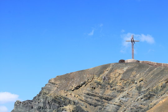 LOW ANGLE VIEW OF CROSS ON MOUNTAIN AGAINST BLUE SKY