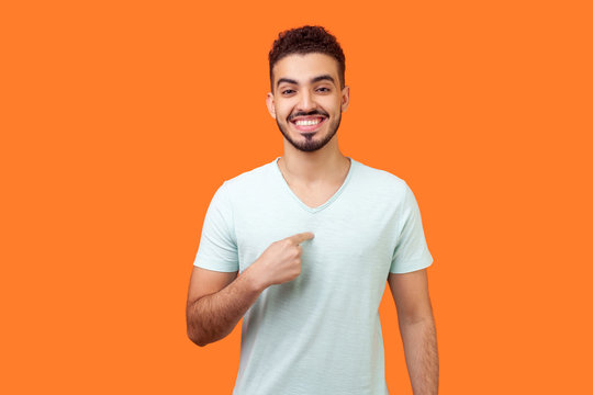 This is me! Portrait of glad satisfied brunette man with beard in white t-shirt pointing at himself, looking at camera with proud and boastful smile. indoor studio shot isolated on orange background