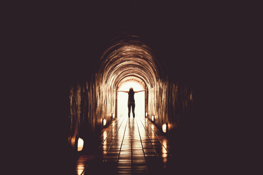 Rear View Of Woman Standing In Illuminated Tunnel