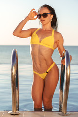 Brunette woman fitness model in yellow bikini coming out of pool