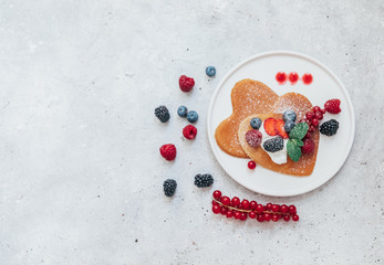 Homemade heart shaped pancakes with berries. Breakfast or brunch for Valentine's Day. Top view, Flat Lay