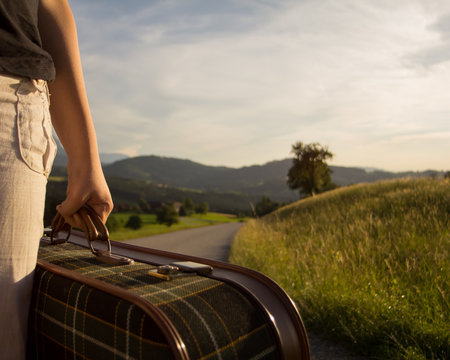 Midsection Of Woman Holding Suitcase On Road Against Sky