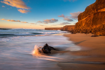 Beautiful sunset at the ocean beach under a rocky cliff, cliff coast south of El Cotillo, Canary Islands, Fuerteventura