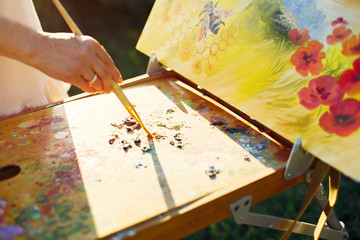 Woman artist painting with oil. Paints in a field